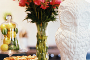 A white owl figurine and a vase of flowers on a kitchen island