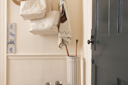 Brass coat hooks and a pillar-like umbrella stand in a Hamptons mudroom