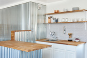 A small kitchen with a tiled wall and wooden countertops.