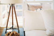 A tripod table lamp next to a white couch