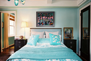 Blue patterned bedding paired with an upholstered headboard