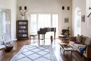 A neutral-hued living room filled with midcentury modern decor and musical instruments