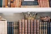 Books and crowns arranged on white shelves
