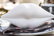 A sculpture of white lips on an outdoor dining table