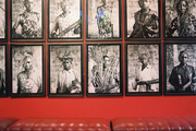 A series of black-and-white photos in a red hallway