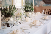 A Thanksgiving-themed dining table decorated with white pumpkins and mercury-glass vases of flowers