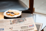 Stacked newspaper and snacks on coffee table.