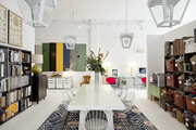 A white conference table with wire-backed chairs on an area rug at Buckingham Interiors + Design in Chicago