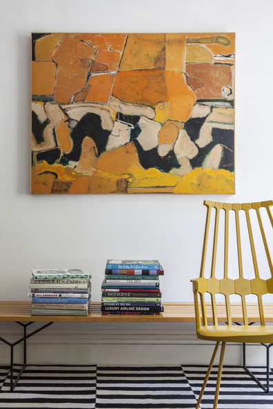 Area Rug - A bench topped with stacks of books beside a yellow chair