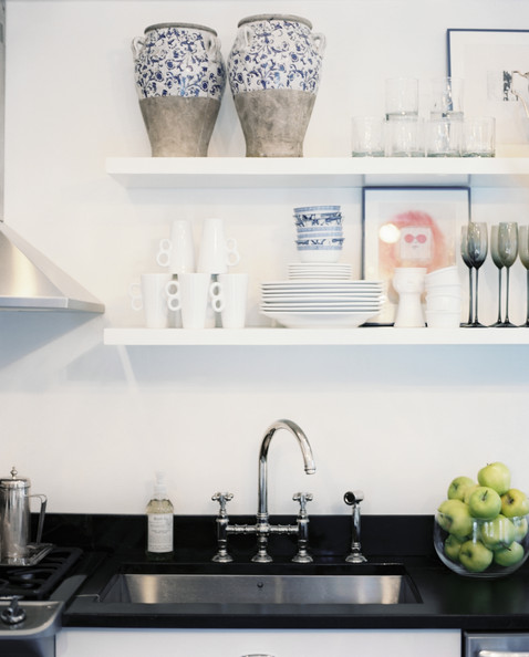 Ari Heckman - Open shelving above black countertops in a kitchen