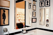 Framed silhouettes and a monogrammed hand towel in  a bathroom with white subway tile