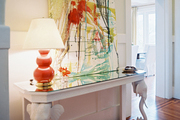 An orange lamp and patterned rug balanced by a white elephant-motif console table