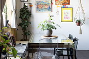 An eclectic dining room with white walls and art.