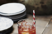 Cocktail and plates atop wooden table.