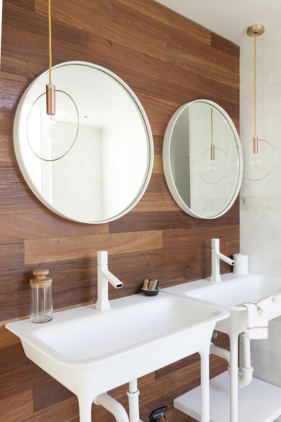 Bathroom - Twinned hanging lamps, round mirrors, and white sinks against a wood-paneled bathroom wall