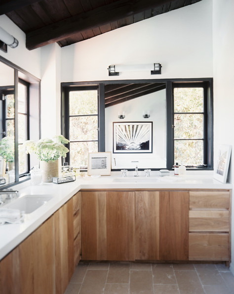 bathroom wood cabinets and a white marble counter in a light filled