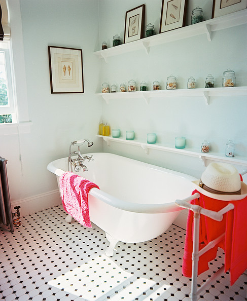 Bathroom - A claw-foot tub soaks up the sun next to jars of seashells and a patterned tile floor.