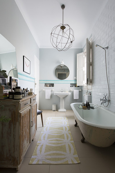 Bathroom - A round mirror and footed tub in a tile-walled bathroom