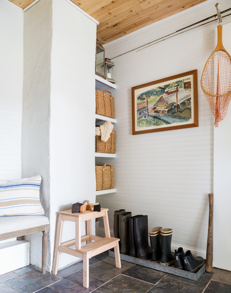 Beadboard - A mudroom with white walls and slate tile floors