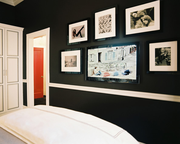 Bedroom - Black walls in a bedroom filled with black-and-white photographs