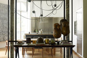 A kitchen with a contemporary light fixture, African art, and a clear glass divider to the living room
