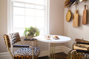 Hat racks above animal print seating and a round table.