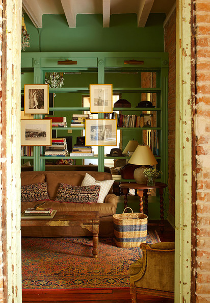 Bohemian Bookshelf - A green library and living room with built-in mirrored bookcases in a historic New Orleans home