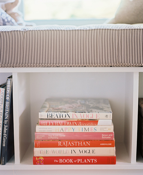 Bookshelf - Vintage design books are artfully stacked below a ticking-stripe window seat.