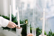 A detail of someone lighting a Hanukkah menorah.