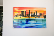 A painting of a cityscape hanging on a wall.