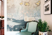 An upholstered armchair next to a garden stool, with scenic Gracie wallpaper in the background