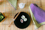 Sushi on a black plate on a woven table.
