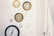 A grouping of clock faces and pocket watches hung on a white wall