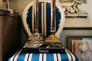 A striped chair topped with books and candlesticks