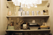 Open shelving holding barware and tabletop accessories
