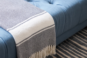 Striped textiles and tufted couch atop a striped area rug.