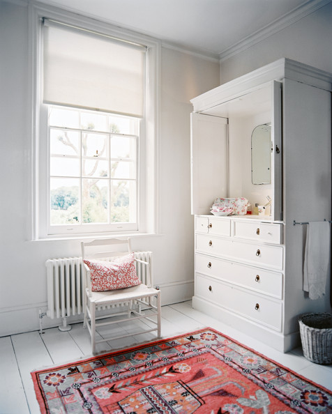 Cath Kidston - A patterned rug in a room with a white armoire and a white chair