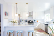 A contemporary kitchen with white cabinets and blue and white stools.