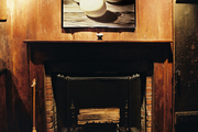 Framed art on rustic wooden walls above a fireplace