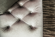 A detail of a contemporary tufted gray bench.