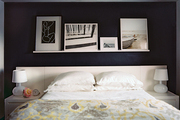 Black walls, framed art, and white bedding in a bedroom
