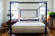 A metal canopy bed with a midcentury chair against white brick walls