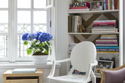White seat and modern tables in front of white bookshelf