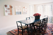 A wooden dining table and chairs atop a patterned rug