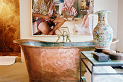 A large-scale photograph hung above a copper tub