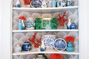 Blue-and-white porcelain, coral, and malachite in a corner cabinet
