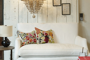 A beaded chandelier hung above a white settee and a black tufted ottoman