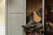 Leather saddlery spilling out of a gray cabinet
