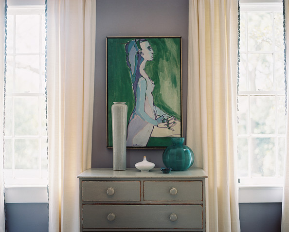 Decor - White curtains and a gray dresser decorated with art and pottery