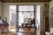A clear glass divider between living area and kitchen, with a table topped with African art and coffee-table books